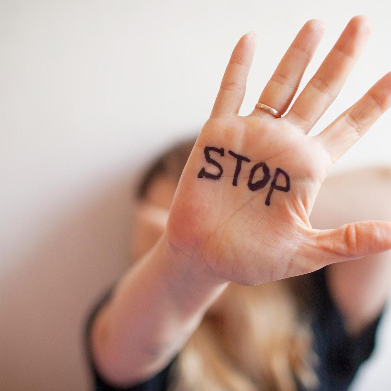 Stop écrit dans la main